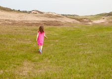 Small girl walking into a dune landscape Stock Photo
