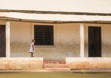 A small girl walks on wall of school in Kenya Royalty Free Stock Images