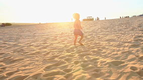 Small Girl Walks Barefooted on Sand Dunes Stops Tired at Sunset stock video footage