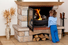 Small girl warms by the fireplace Royalty Free Stock Image