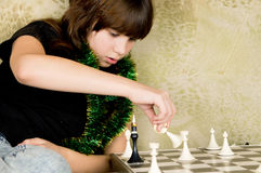 Small the girl was sitting on the sofa at and plays chess Royalty Free Stock Photography