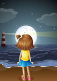 A small girl watching the fullmoon at the beach Royalty Free Stock Images