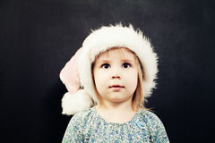Small Girl wearing Santa Hat looking up. Cute Christmas Child Royalty Free Stock Photography