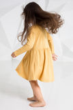 Small girl wearing yellow dress dancing in studio against white background. Royalty Free Stock Photo