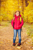 Small girl wears rucksack and stands in forest Royalty Free Stock Image