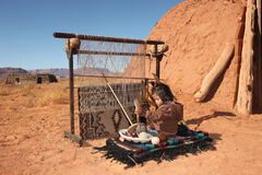Small Girl Weaving Blanket. Image of a young Native American girl using a loom to weave a blanket. She is looking away from the camera and full length viewable Royalty Free Stock Images