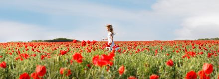 Small girl in white dress running in poppies Royalty Free Stock Images