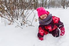 Small girl among winter bushes Stock Image