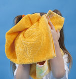 Small girl is wiping its face by towel isolated. On blue background Stock Photos