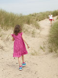 Small girl and woman walking through sand dunes royalty free stock photo