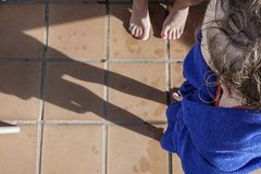 Small girl wrapped in towel on the edge of the pool stock photos