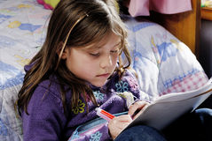Small Girl writing. Drawing or doing a homework at home royalty free stock images