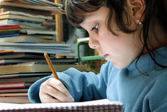 Small girl writing. Over a table royalty free stock photo