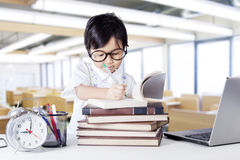 Small girl writing on book in the class Royalty Free Stock Image