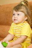 Small girl in yellow eat green apple Stock Photo