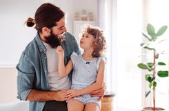 A small girl with young father at home, talking. Copy space. A cute small girl with young father at home, talking. Copy space royalty free stock image