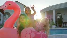 Small girlfriends on summer vacation, sweet girls lie on inflatable pink flamingo near pool, spoiled rich childs in stock footage