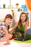 Small girls with computer at home Stock Images