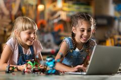Girls cooperating while making a robot Royalty Free Stock Images