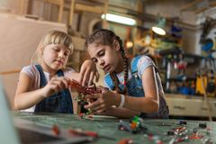 Young girls building toy construction machine Royalty Free Stock Photos