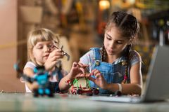 Young girls building toy construction machine Stock Image