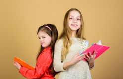 Small girls with note books. Friendship and sisterhood. workbooks for writing. Back to school. students reading a book royalty free stock photography