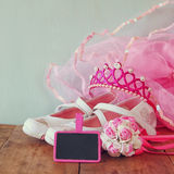 Small girls party outfit: white shoes, crown and wand flowers on wooden table. bridesmaid or fairy costume Stock Photo