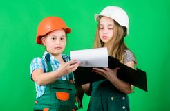 Small girls repairing together in workshop. school project. Happy children. Little kids in helmet with tablet. Labor day stock photography