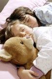 Small girls sleeping. And embracing a felt bear Stock Photo