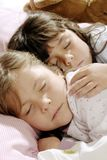Small girls sleeping. Two small girls sleeping together, while one is embracing the other Stock Image