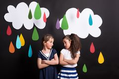 Small girls in studio, standing against black background with clouds and raindrops. Stock Photography