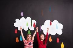 Small girls in studio, standing against black background with clouds and raindrops. Stock Images