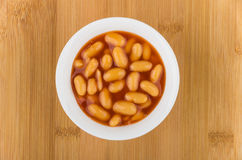 Small glass bowl with beans in tomato sauce on board Stock Images