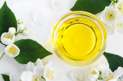 Small glass bowl with cosmetic/massage/cleansing jasmine aroma oil. Copy space. Small glass bowl with cosmetic/massage/cleansing jasmine aroma oil. Top view royalty free stock images
