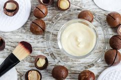 Small glass bowl with facial or hair mask moisturizer, body butter with macadamia oil. Natural cosmetics ingredients. stock photos