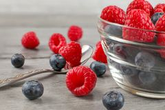 Small glass bowl full of blueberries and raspberries mix, some s. Pilled on gray wood desk with silver spoon Stock Photos