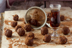 Small glass of brandy, gauze and homemade candies wooden table Stock Photo