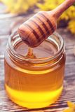 Small glass jar with liquid honey. A small glass jar with liquid honey on a wooden table royalty free stock images