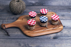 Small glass jars lids with fruit or berry jam Stock Images