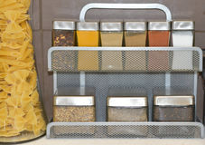 Small glass jars with spices and other kitchen condiments on a kitchen shelf Royalty Free Stock Photography