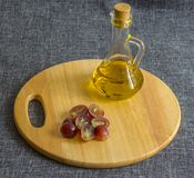 A small glass jug with oil, chopped grapes. On a wooden cutting board royalty free stock image