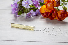 Small glass tube with homeopathy globules Stock Photo