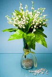 Small glass vase with may flowers on blue Royalty Free Stock Photography