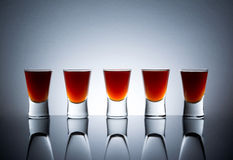 Small glasses, drink shots of alcohol with reflection Royalty Free Stock Images