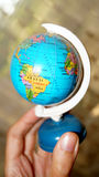 Small globe with maps of South America in the hand Stock Image