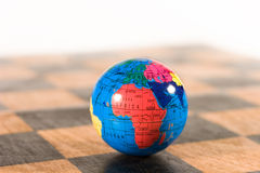 Small Globe On An Old Chessboard Royalty Free Stock Photo