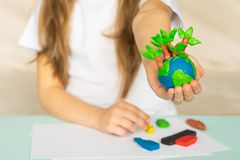 A small globe with trees in the hands of a child. Layout of the planet made of plasticine in children`s palms. Concept stock photo