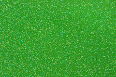 Small Gold/Aqua/Black/White Glitter on Green Background Stock Image