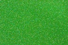 Small Gold/Aqua/Black/White Glitter on Green Background. Macro photo of small gold, aqua, black, and white glitter on a green background Stock Image