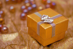 Small gold christmas gift. Gold box with silver ribbon and shiny background Stock Photos